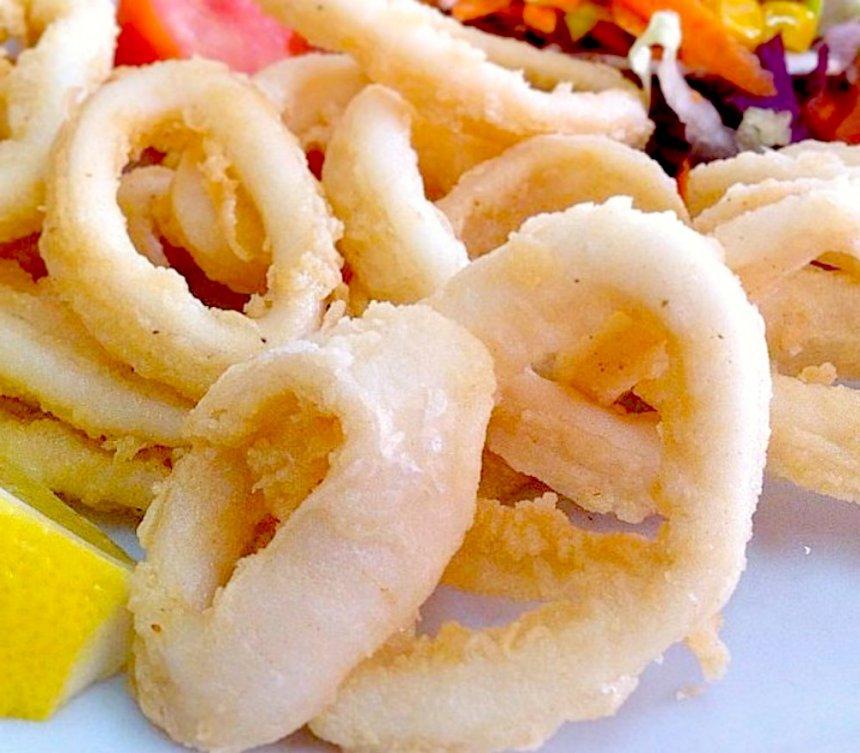 Aros de calamar fritos con salsa de maíz y queso