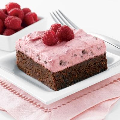 Mousse de frambuesas encima de brownie de nueces y crema inglesa