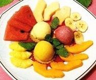 Postre de sorbetes y frutas tropicales con coulis